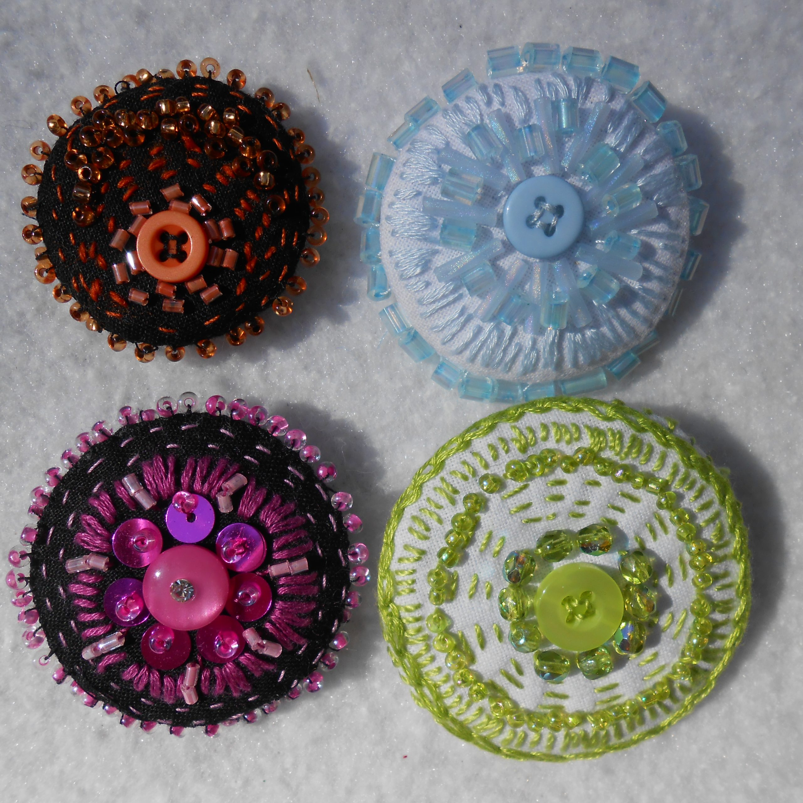 Photo 7 - Four versions of brooches with beaded or embroidered edges.